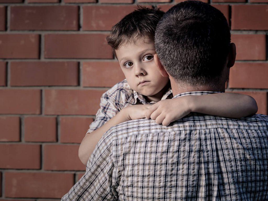 Portrait of sad son hugging his dad